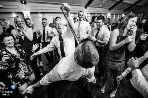 婚礼接待摄影| 来宾在新泽西州莫霍克湖乡村俱乐部的舞池上抓住另一位客人的领带