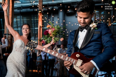 Toronto Reception Photography - The bride is dancing next to the groom playing an electric guitar.