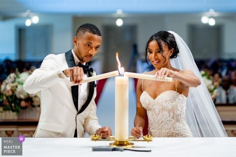 Fotografía de bodas en la Universidad de Maryland, College Park, MD, EE. UU. - Una novia y el novio encienden su vela de la unidad