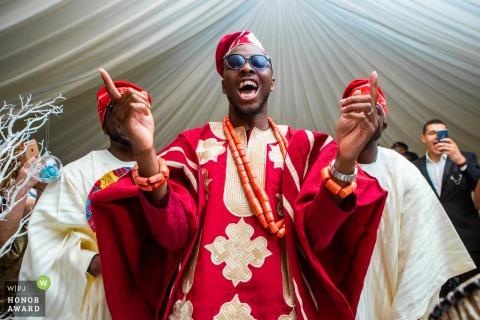 Trouwfoto in Londen in het huis van de bruidegom - Bruidegom danst op zijn traditionele Nigeriaanse bruiloft