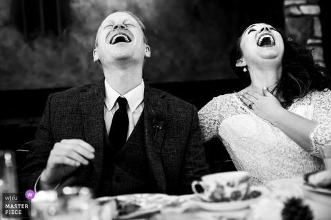 Lodge à Cathedral Pines (Colorado Springs, CO) | Jeunes mariés riant de façon incontrôlable pendant le toast du meilleur homme.