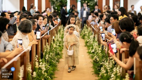 Flowergirls walk down the aisle during the wedding ceremony at Wattana Church, while many of the guests take pictures with their phones.