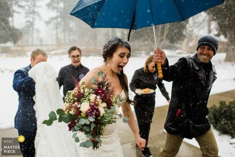 Colorado photo de mariage de la mariée marchant à l'intérieur pour se réchauffer de la neige.