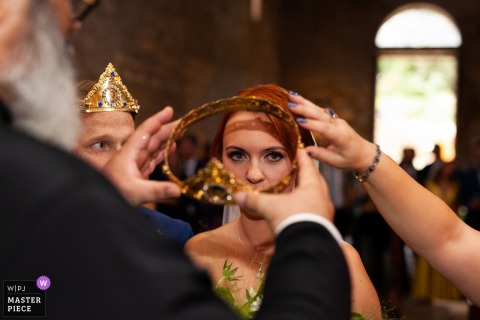 abbazia di San Giusto - Tuscania- Italy wedding photos | The bride is not very convinced during her coronation in the Orthodox ceremony