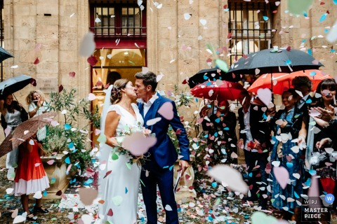 Wedding in Aix-en-Provence   Photo of the grand exit for the bride and groom under umbrellas