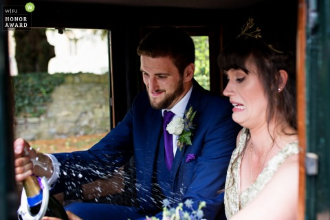Wedding photo outside the Pershore church - Groom opening a champagne in the carriage
