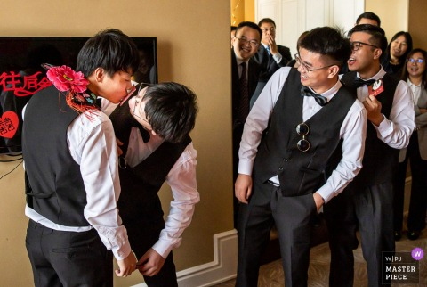 Beijing wedding party game of two men kissing with a card inbetween their lips.