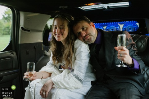 Wedding photo In a Limo in Altamont, NY - A bride and groom snuggle while holding champagne glasses as they ride in a limo to their reception.