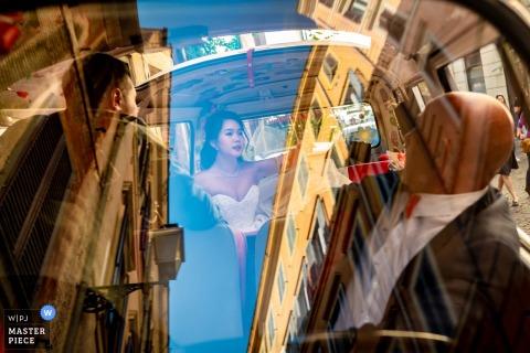 Rome, Italië trouwdag fotografie in de auto | Daar was de weerspiegeling van de gebouwen en de lucht van de stad op de voorruit en de bruid was in gesprek met de chauffeur over waar de volgende bestemming zal zijn.