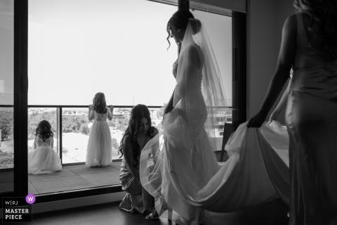 Fotograf ślubny z Melbourne: gdy panna młoda nosi buty, dziewczęta z kwiatami obserwują inne dzieci bawiące się na placu zabaw.