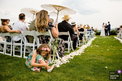 Coeur d'Alene, Idaho Outdoor Wedding Ceremony Photography | A young wedding guests entertains herself during the ceremony.