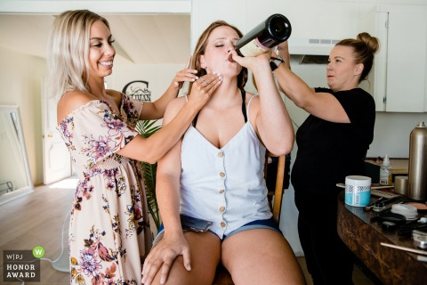 Sagle, Idaho wedding photo - The bride enjoys a drink as she prepares for her wedding day surrounded by hair and makeup artists.