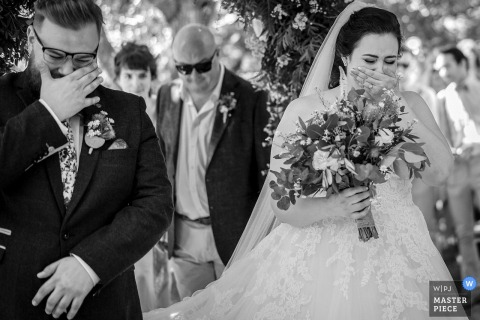 Cornish Tipi Weddings, Cornwall, UK Wedding Reportage Photographer: Synchronized Bride & Groom bursting into tears upon seeing each other at beginning of wedding ceremony. Both individuals mirror each other wiping away tears with their outer hands.