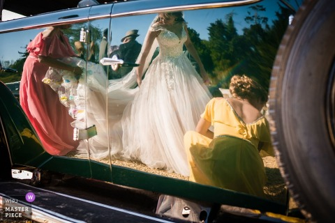 Beaulieu Abbey, Hampshire, UK wedding reportage photographer: A reflection of bride Giselle in the vintage car door. Having arrived at the Abbey her bridesmaids arranging her dress.
