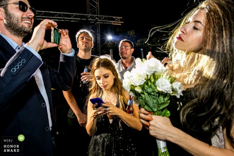 Wyndham Ankara photographer said: Boy with sunglasses (during midnight) is trying to take a girls photo who caught the bouquet, a boy is staring that girl and another boy next to him is looking that boy and a girl is playing with her phone in the middle