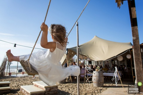 Zandvoort Safarilodge, reception venue photo of a young bridesmaid on swing