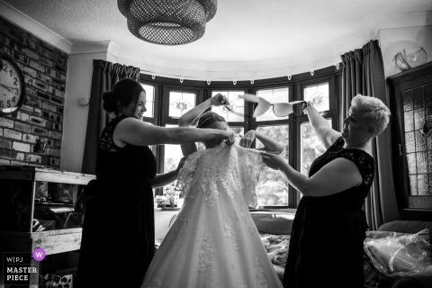 Halesowen Bridedsmaids removing brides Bra during bridal prep - Wedding photos at getting ready