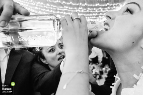 Alcoy party photo from the wedding reception of a woman drinking from a bottle.