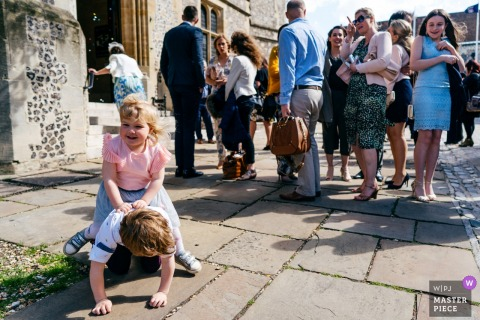 Winchester Registry Office wedding reportage | A little girl riding her brother whilst guests exit ceremony location