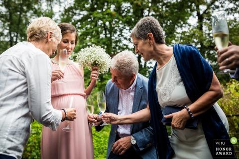 Brno trouwfoto buiten - Oudere gasten bieden drinken Cheers aan het ongeboren kleinkind