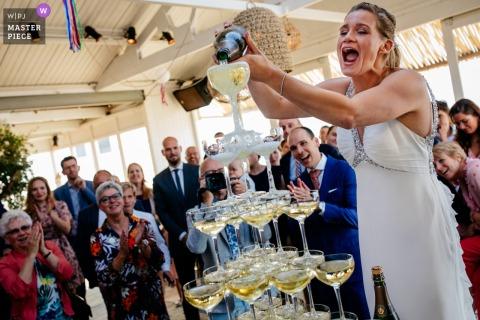 Hochzeitsfotografie in Witsand, Noordwijk, Niederlande | Champagner! Die Braut gießt in den Glasturm