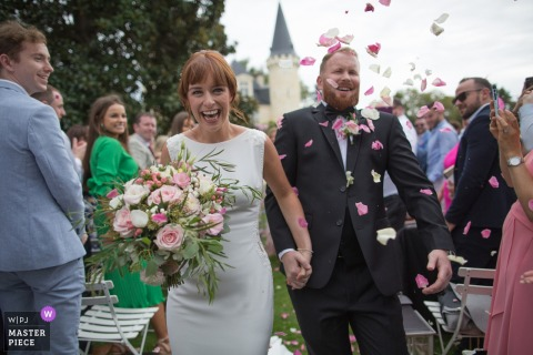 CHATEAU D'AGASSAC LUDON MEDOC CEREMONY PHOTOGRAPHY   BRIDE & GROOM SURPRISED AND AMUSED BY THE PETALS THROWING