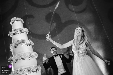 San Diego, Ca La mariée et le marié se préparent à couper le gâteau avec une grande épée.