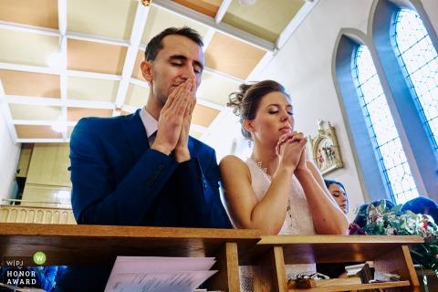 Holy Cross Church, Lichfield-trouwfoto van de kerk van de bruid en bruidegom die samen bidden