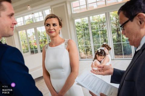 Photographie de la chapelle de mariage des Bahamas | La fille de la mariée et la fille du marié s'embrassent alors que les anneaux sont présentés