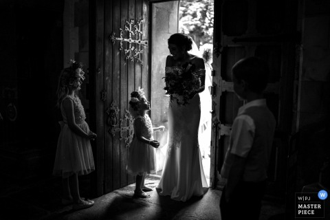 Wimborne Minster, Dorset wedding reportage photography | Flower Girl wishes Bride luck as she arrives to get married