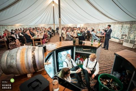 Photographie à la ferme familiale près d'Oxford - Le personnel du bar de réception de mariage se cache pendant les discours