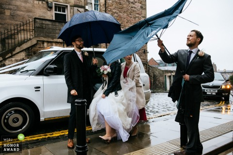 Scotland rainy day at the Edinburgh city centre wedding photography - Bride, groom and bridal party getting out of the taxi