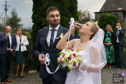 Malopolskie hotel photography after the wedding | The groom and bride are drinking champagne