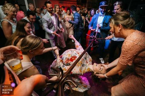 Hochzeitsfotografie aus Flandern am Empfangsort - Jemand hat sich einen Kleiderbügel ausgesucht und alle damit beauftragt, das Limbotanzen darunter zu beginnen!