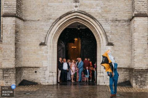 Hochzeitsfotografie der Antwerpener Kirche   Alle hatten bereits Schutz in der Kirche gesucht, als es plötzlich anfing zu strömen. Nur ein Typ hatte Probleme, seinen Regenschirm zu schließen, weil der Wind heftig wehte.