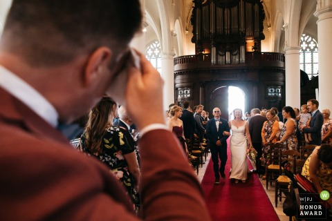 Antwerpen Church wedding photojournalism - The groom wipes his forehead, as he started sweating heavily during the entrance in church of his wife-to-be.