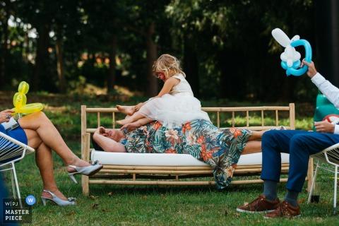 Photographie du lieu de réception en Flandre | Un enfant essaie d'attirer l'attention de sa grand-mère pendant qu'elle essaie de faire une sieste entre 2 réceptions.