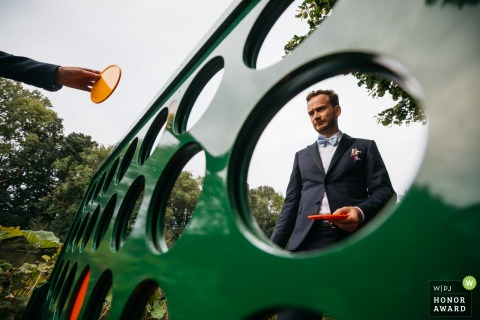 Flanders reception venue photography - The groom is in deep thoughts to plan his next move in this giant 4-in-a-row game.