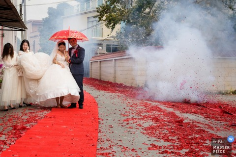 Guangdong wedding day photography of bride walking past firecrackers at home