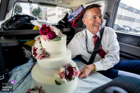 Woodend Sanctuary, Chevy Chase MD wedding photography | Father of the bride rides in the back seat of the car with the three tier cake his daughter, the bride, made from scratch.