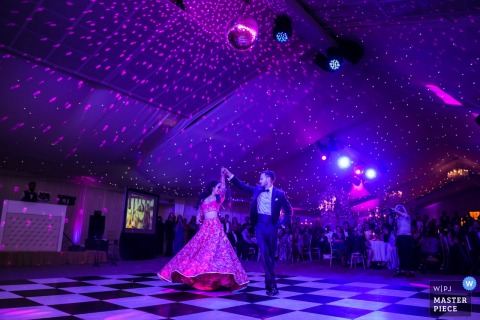England wedding photography at Ditton Park Manor venue | First dance for the bride and groom under purple lights.