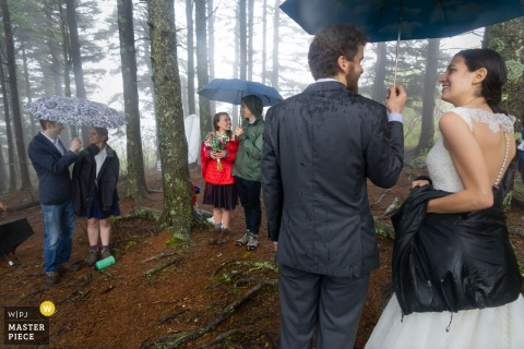 Black Balsam Knob, NC rainy day outdoor wedding photo of couples talking to each under their own umbrellas