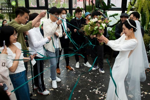 China wedding photo from the Ceremony Location showing The process of drawing a ribbon to get a bouquet.
