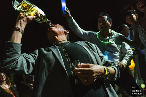 Mexico wedding photo from Las Caletas, Puerto Vallarta of The godfather of the bride drinking Mexican water