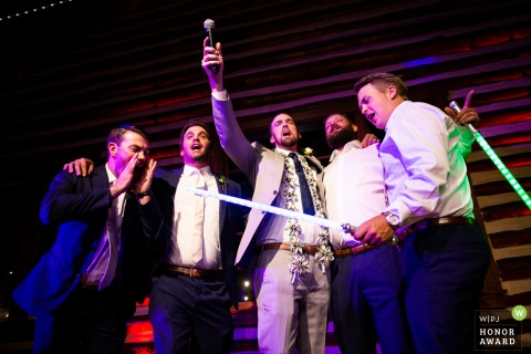 Wedding photography from Hudson Gardens, Denver, Colorado of Groomsman flanking the groom as he belts out a classic karaoke song