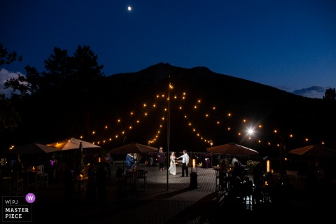 Della Terra Mountain Chateau, Estes Park Colorado Wedding Photo |	The bride and groom share their first dance under the market lights and the stars.