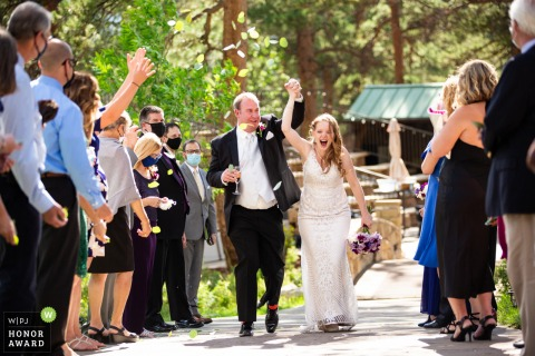 Wedding photo from Della Terra Mountain Chateau, Estes Park Colorado showing the couple is Elated to finally be married, the couple shrieks with joy as their guests toss aspen leaves over them