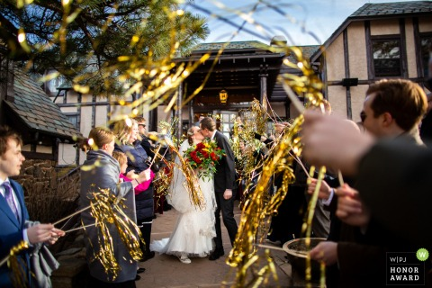 CO wedding photography from the Boettcher Mansion, Golden Colorado showing Guests line the exit path with wild gold streamers to congratulate the couple after their ceremony
