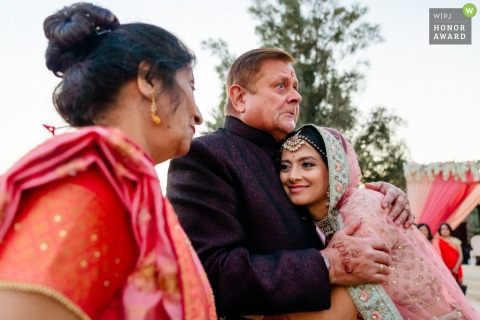 Wedding photo from Meliá Desert Palm Dubai showing the Bride hugs father farewell at an Indian wedding