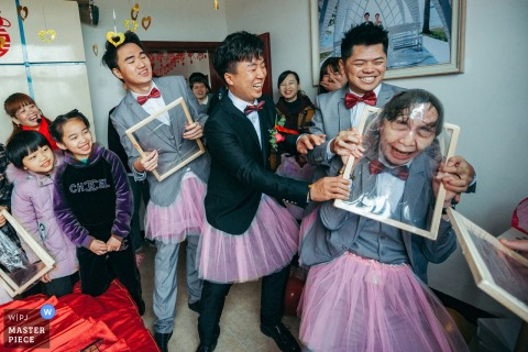 Fujian Wedding Photo of the groom and his groomsmen smashing their faces through cellophane wrapped frames